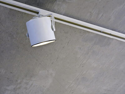 Accent light in recessed white track on stained gray ceiling above contemporary art exhibit