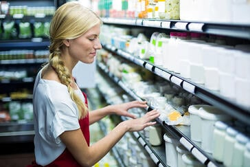 Female staff checking grocery products in shelf of supermarket-1